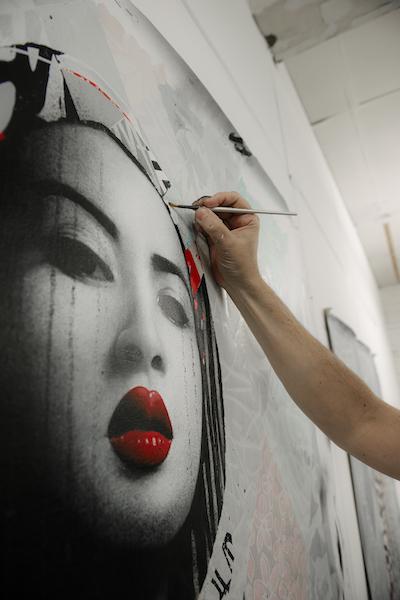 Photographie de Hush peignant l'un de ses portraits